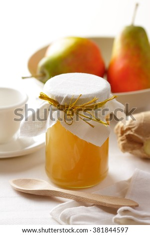 A jar of homemade pear jam and ripe pears on a breakfast table. - stock photo