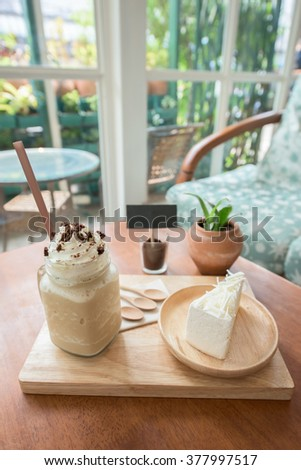 A jar of Mocha and piece of white chocolate cake in pastel living room - stock photo