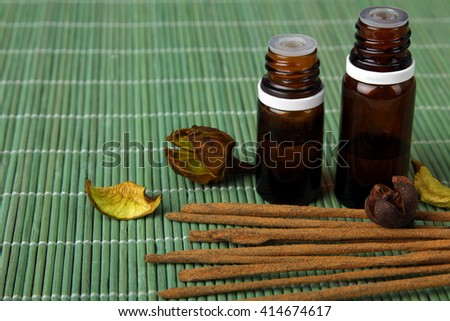 a jars with essential oils with incense on green wooden background - stock photo