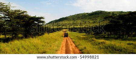 A jeep traveling on a dirt road in africa - stock photo