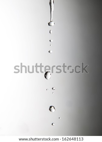 a jet of water on a gray background - stock photo