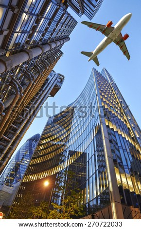 A jet plane flying low over Three different kind of architecture with commercial office buildings exterior. Evening view at bottom skyscraper - stock photo