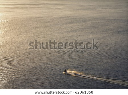 A jet ski sailing alone in the open sea. Great feeling of freedom - stock photo