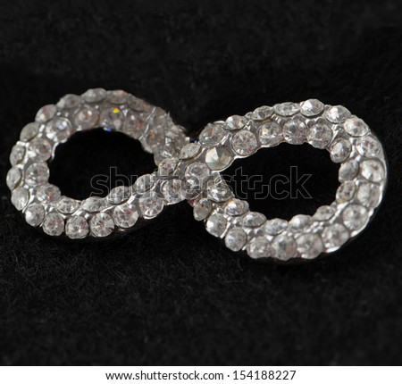 A jewel in form of infinity symbol over black background - stock photo