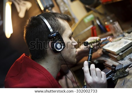a jeweler behind a desk solder product - stock photo