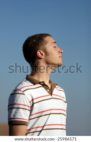 A Jewish Young Adult with a knitted skull cap looks up - stock photo