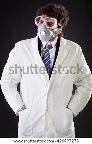 a joung and handsome doctor or researcher with a white lab coat and a protective mask - stock photo