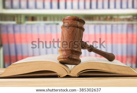 A judges gavel on top of the pages law book in a courtroom. concept of law. - stock photo
