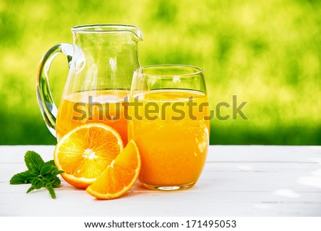 A jug and glass of freshly squeezed orange juice, garnished with a sprig of mint and slices of orange, in an outdoor setting during summer. - stock photo