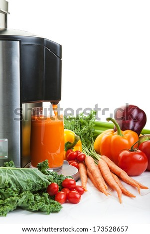 A Juicer surrounded by healthy fruits and vegetables on white with shadows. - stock photo