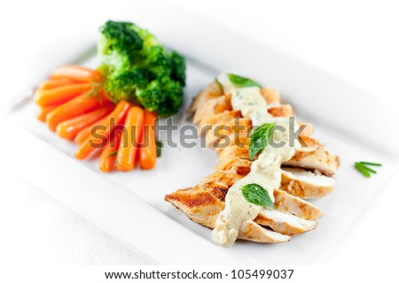 A juicy chicken breast grilled and topped with alfredo sauce and steamed carrots and broccoli as side dish. Shallow depth of field on first slices of chicken - stock photo