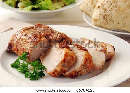 A juicy fresh pork loin roast sliced on a plate - stock photo
