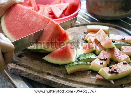 A juicy watermelon is cut open with a metallic knife on a wooden cutting plate - stock photo