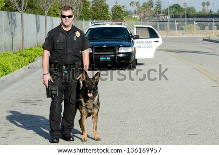 A K9 police officer standing with his partner with their patrol car in the background. - stock photo