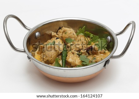A kadai serving bowl of balti chicken pasanda curry, garnished with coriander leaves and a green chilli. This curry is made with yoghurt , cream and chopped coriander as well as the usual spices, - stock photo