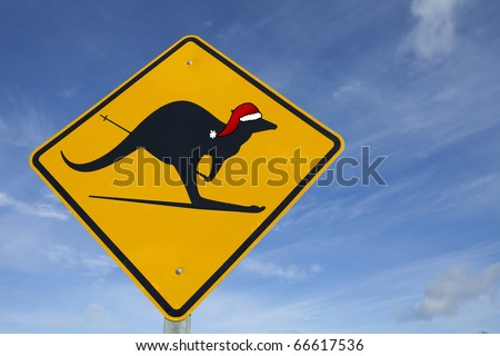 A kangaroo sign in Australia with a santa hat and skis - stock photo