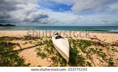 A kayak left stranded on the tropical beach. - stock photo