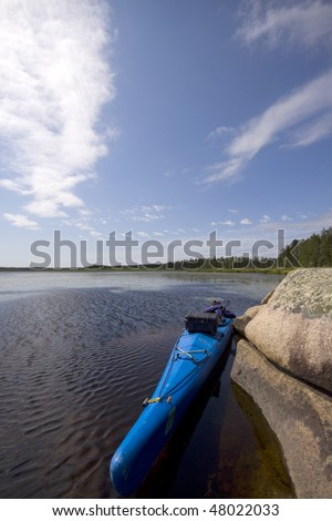 A kayak sits beside a rock on a large lake. - stock photo