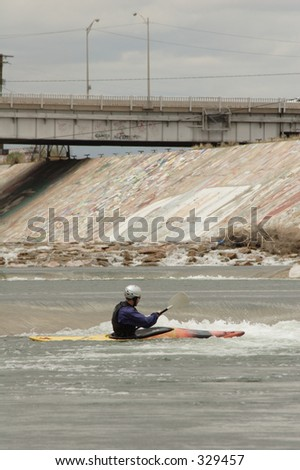 A kayaker plunges through the artificial rapids created on the Arkansas River near downtown Pueblo, Co., taken in May, 2005 - stock photo