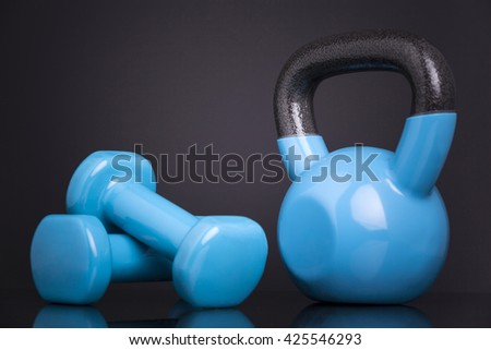 A kettlebell and two dumbbells on black background - stock photo
