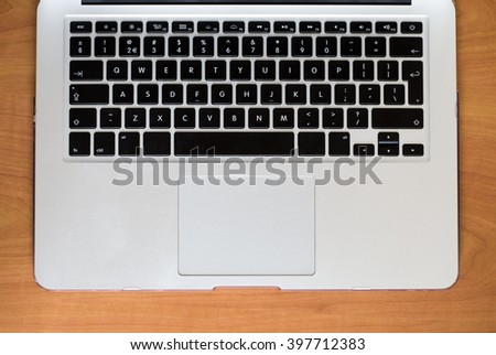 A keyboard of a laptop computer on a wooden table - stock photo