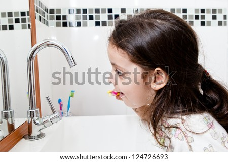 A kid girl brushing her teeth on a bath room and looking to the mirror. - stock photo