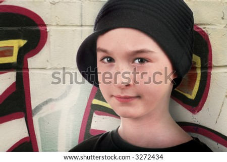 a kid in the street standing against a wall with graffiti and trying to look tough - stock photo