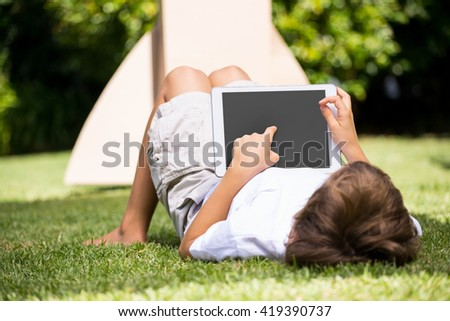 A kid is lying with a tablet computer in a garden - stock photo