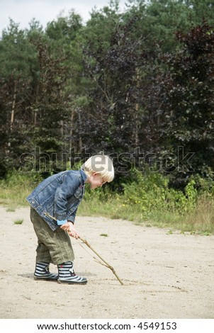A kid is writing with a stick in the sand - stock photo