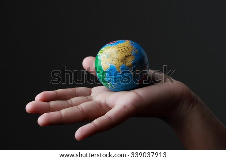A kid's hand holding a globe in a dark background - stock photo