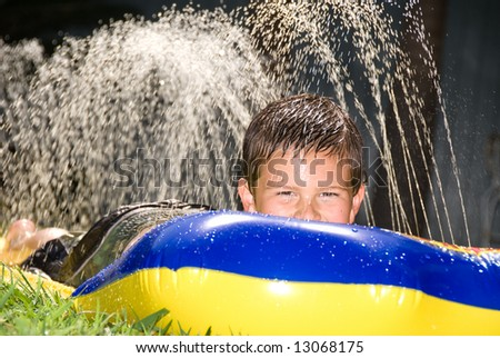 A kid slides down a slippery water slider during a hot summer day. - stock photo
