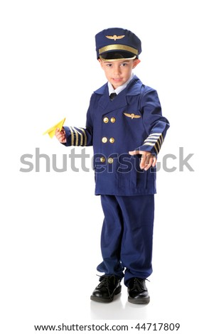 A kindergarten boy in an over sized airline pilot uniform ready to launch a paper airplane. - stock photo