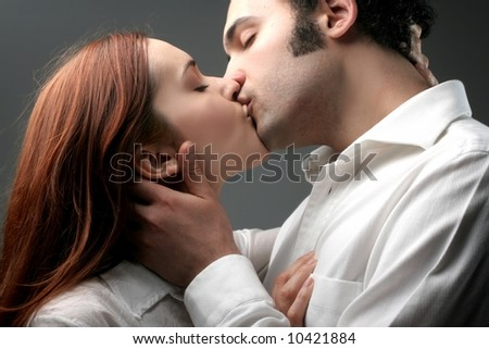 a kiss of a young couple - stock photo