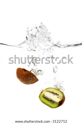 a kiwi fruit is falling in water with a big splash and a lot of water drops - stock photo