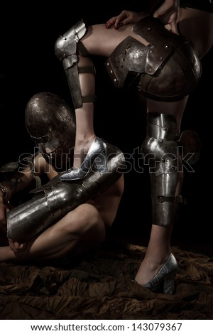 A knight in armour worshiping and holding female leg - stock photo