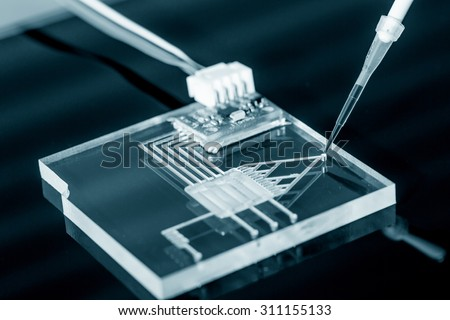 A lab on chip is device integrates several laboratory processes in one device, mostly LOC based on glass plate. - stock photo