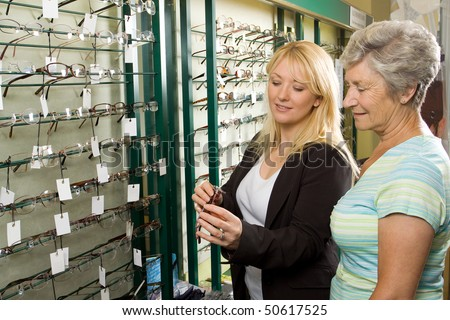 A lady choosing a pair of glasses in an optician - stock photo