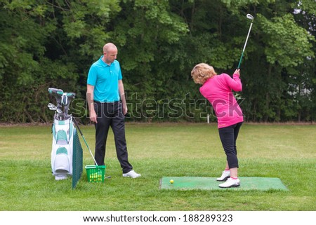 A lady golfer being taught to play golf by a Pro on a practice driving range. - stock photo