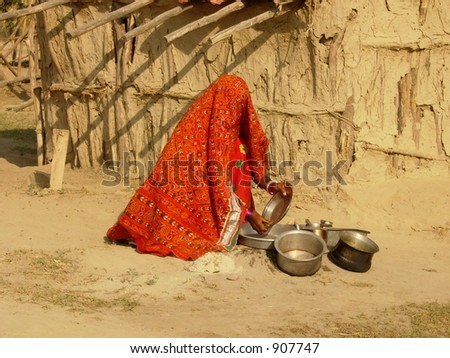 a lady washing utensils in a village in india - stock photo