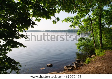 a lake framed by shoreline and trees with green leaves - stock photo
