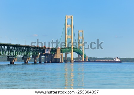 A lake freighter crossing under the Mackinac Bridge, heading from Lake Huron to Lake Michigan - stock photo