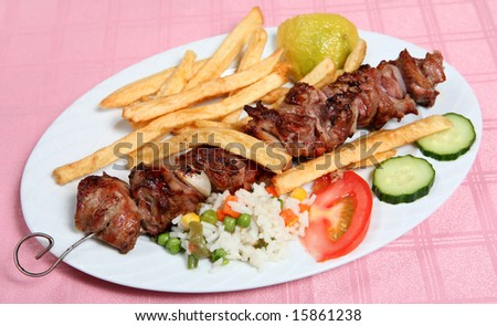 A lamb souvlaki, or kebab, on the skewer, served with french fried potato chips, rice and vegetables at a taverna. - stock photo