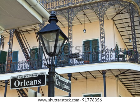 A lamp post and wrought iron balconies at the corner of Orleans and Dauphine streets in the French Quarter of New Orleans - stock photo