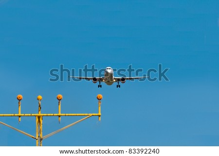 A landing airplane with landing lights on a blue sky - stock photo