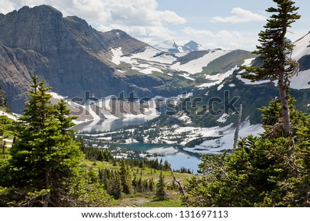 A landscape of rugged mountains with patches of snow melting into Hidden Lake in the valley and framed by evergreen trees. Glacier National Park, Montana. - stock photo