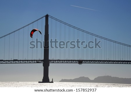 A landscape showing the Golden Gate Bridge in silhouette with a sea surfer and an airliner in the blue sky. - stock photo