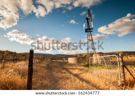 A landscape view of a wind pump and water tank in a farm as a gate stands open and the road leads to it. - stock photo