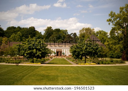 A landscaped garden, with trees and shrubs and a large home in the background. - stock photo