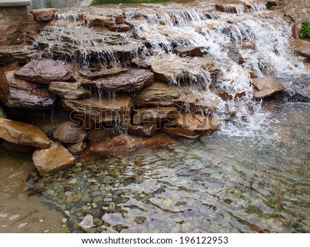 a landscaped waterfall made of stacked rocks - stock photo