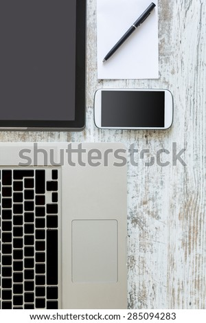 A Laptop computer, a Tablet PC and a Smartphone on a Desktop.  - stock photo